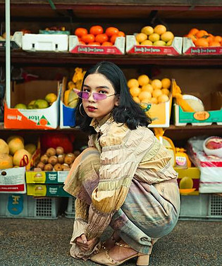 girl with glasses in front of fruit stand